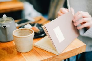 vrouw schrijft in notitieboek met kop thee ernaast